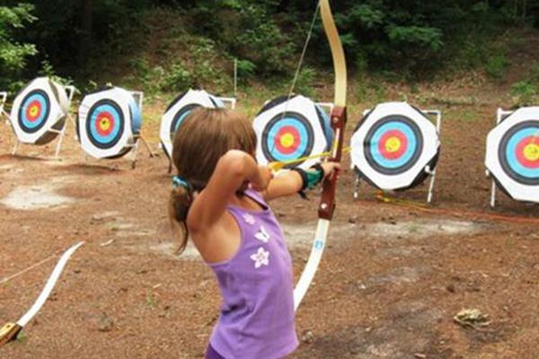 little girl shooting an arrow at targets